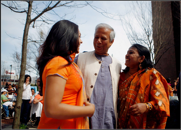 Image of Muhammad Yunus speaking and smiling with two women.